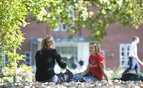 Students sitting on campus grass