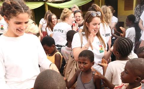Students helping children in Africa