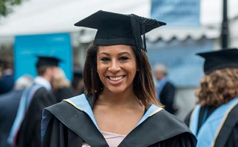 Female graduate smiling to camera.