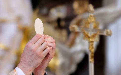 Priest holding up communion wafer