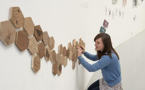 Student setting up a Art exhibit