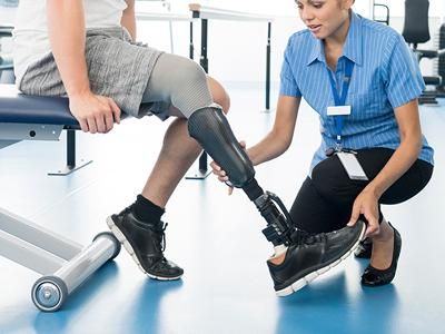 A nurse helping a patient with his prosthetic leg