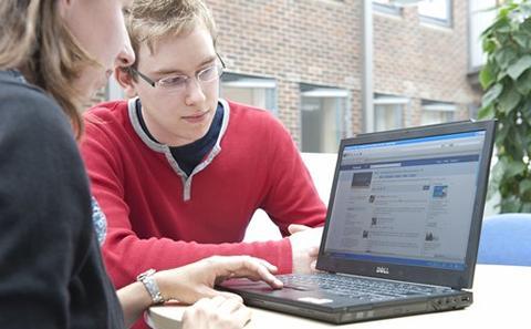 Students sat around a laptop