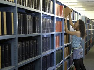 A student getting a book from the shelves