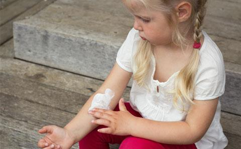 Young child adding cream to her arm