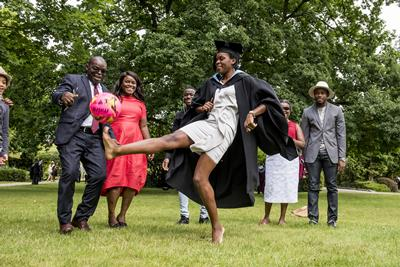 Footballing graduate kicking a ball
