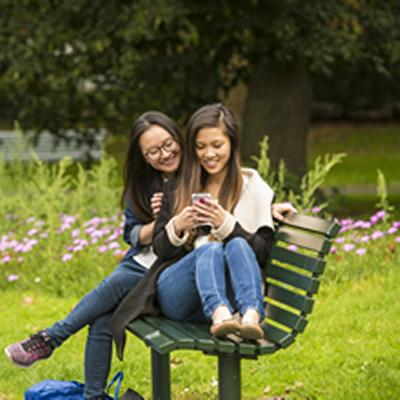 Two women sat on park bench