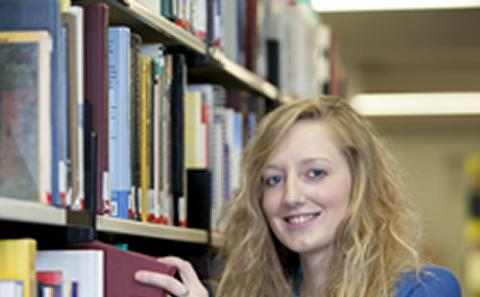 Student takes book from shelf