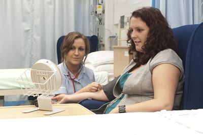 Nurse takes patient's blood pressur