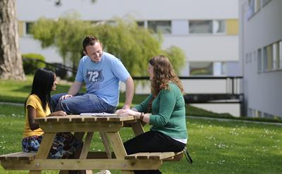 Three students relaxing outdoors