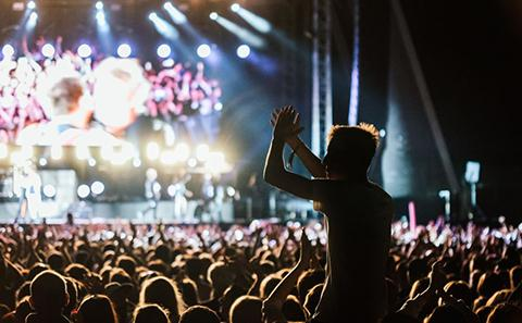 Crowd dancing near a stage at night