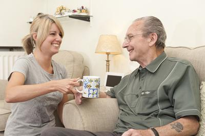 Woman giving cup of tea to man