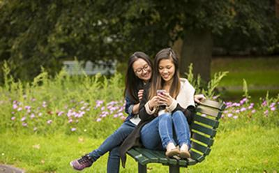 Two females sat on bench