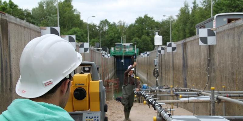 ECE student surveying a prototype beach in the Delta Flume, Netherlands, during the EU Hydralab IV Barrier Dynamics Experiments for his masters project