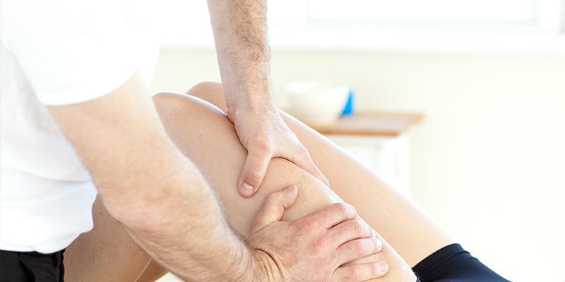 Physiotherapist massaging patient leg