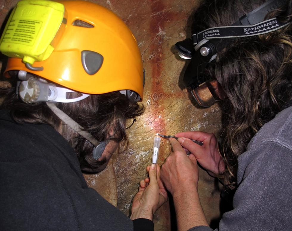 Dirk Hoffmann and Alistair Pike sampling calcite on top of the red scalariform sign in La Pasiega.
